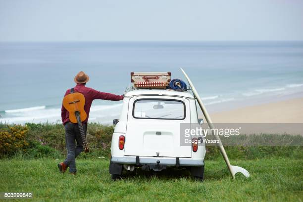 Hipster man on road trip with guitar and surfboard.