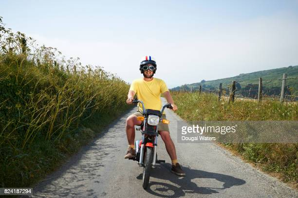 hipster man on vintage bike in countryside. - vintage motorcycle stock pictures, royalty-free photos & images