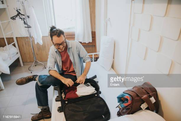 hipster man open suitcase on his vacation - open backpack stock pictures, royalty-free photos & images