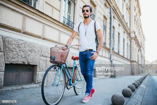 Hipster man pushing bicycle