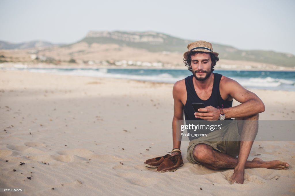 Hipster man sitting at the beach using phone : Stock Photo