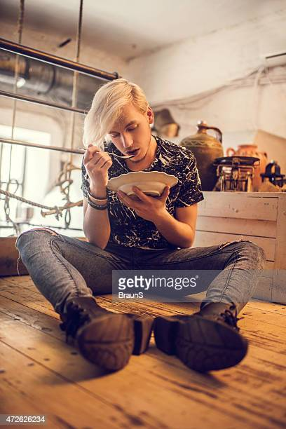 Hipster man sitting on the floor and eating soup.
