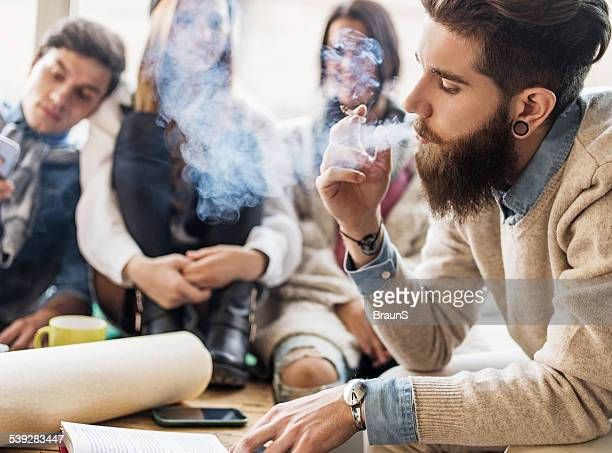 Hipster man smoking cigarette while reading a book.