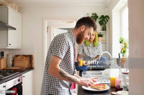 hipster man spreading jam on toast for breakfast - wife stock pictures, royalty-free photos & images