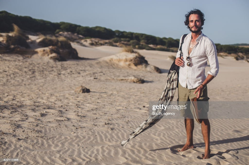 Hipster man standing at the beach : Stock Photo
