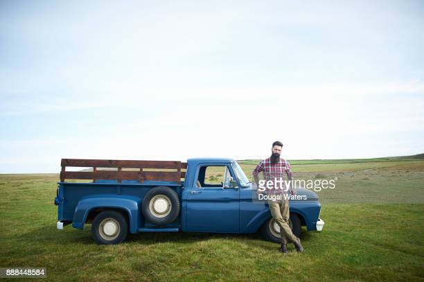 Hipster man standing beside old fashioned vintage truck in countryside.