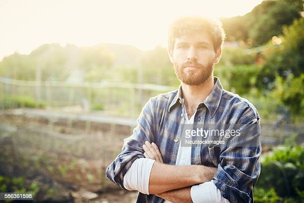 hipster man standing with arms crossed on organic farm - karohemd stock-fotos und bilder