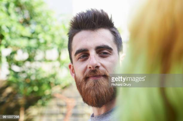 Hipster man talking to his wife in their garden