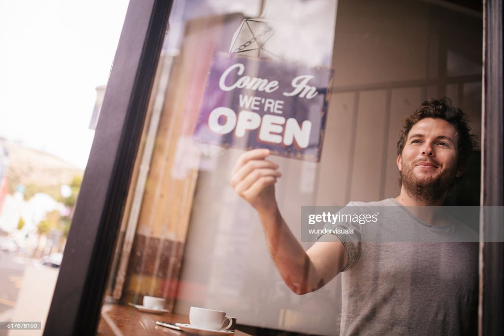 Hipster Man Turning Opening Sign on Door Coffee Shop : Stock Photo