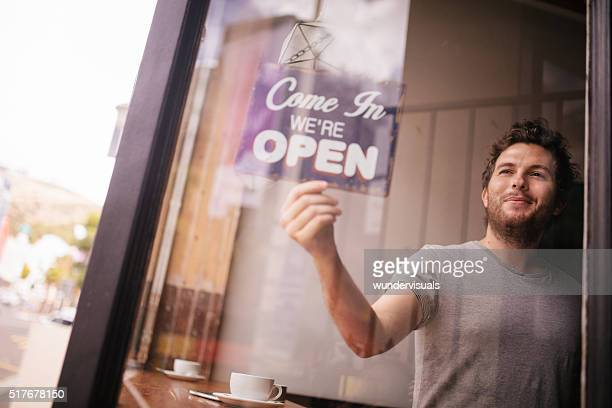 hipster man turning opening sign on door coffee shop - openmaken stockfoto's en -beelden