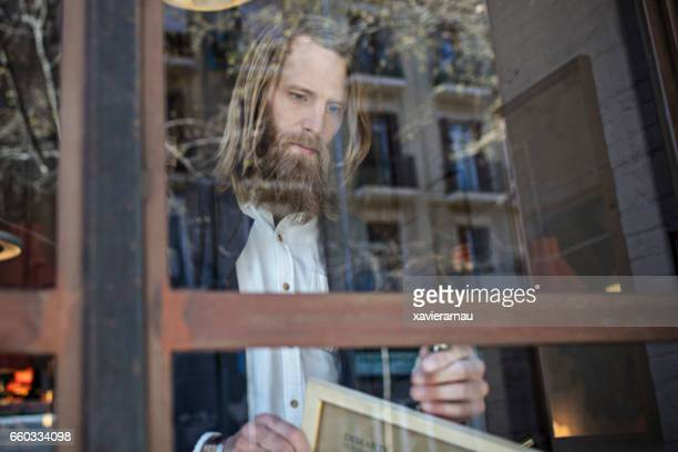 Hipster Man Turning Opening Sign on Door