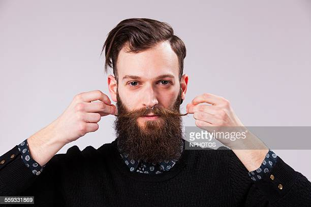 Hipster man twisting his moustache.