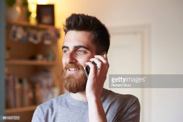 Hipster man using a smart phone in his living room