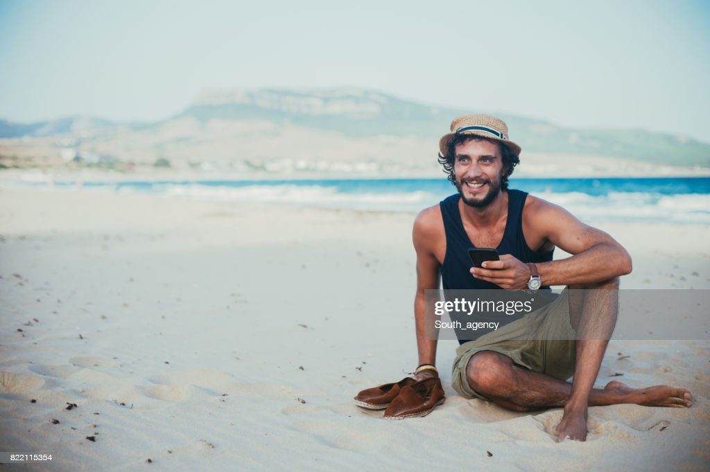 Hipster man using phone at the beach : Stock Photo