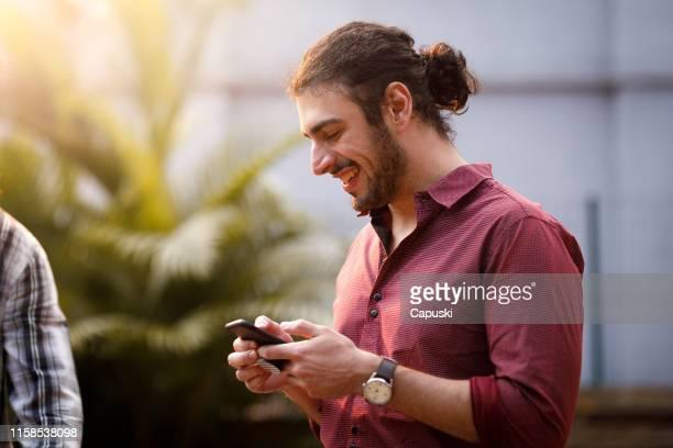 homem do hipster que usa o telefone esperto e o sorriso - coque cabelo para cima - fotografias e filmes do acervo