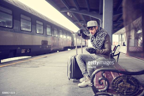 Hipster homme à l'aide de téléphone intelligent à la gare ferroviaire.