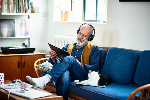 Hipster man wearing headphones listening to record and reading cover - gettyimageskorea