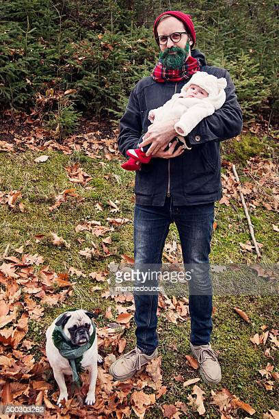 Hipster man with glitter beard holding baby with pug outdoors.