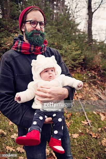 """hipster hombre con verde brillante barba retención bebé al aire libre. - """"martine doucet"""" or martinedoucet fotografías e imágenes de stock"""