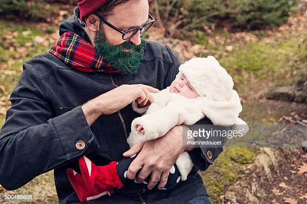Hipster man with green glitter beard holding baby outdoors.