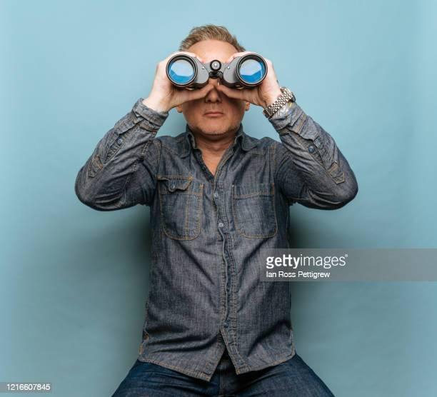 hipster man with tattoos looking through binoculars - binoculars stock pictures, royalty-free photos & images