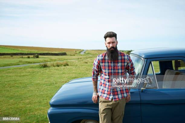 Hipster man with vintage truck in countryside.