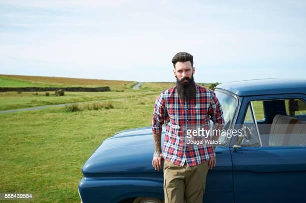 hipster man with vintage truck in countryside. - landfahrzeug stock-fotos und bilder