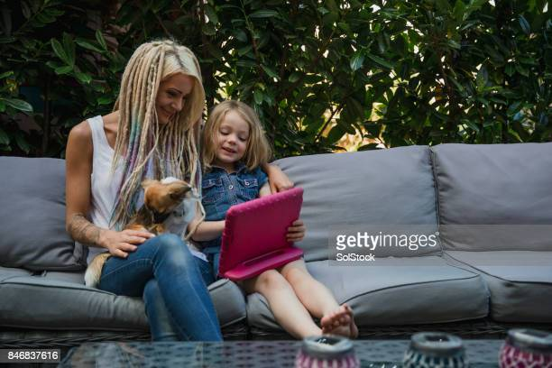 Hipster Mother Sharing a Digital Tablet with Young Daughter