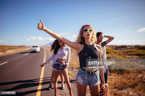 Hipster Multi-Ethnic Group of friends Hitchhiking on Highway