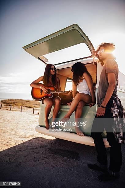 Hipster Multi-ethnische Gruppe spielt Gitarre am Strand