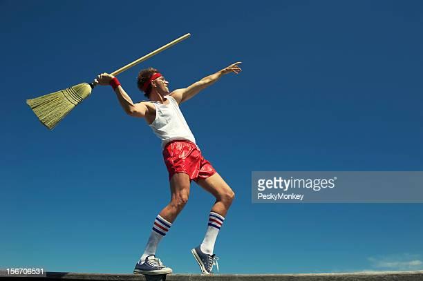 Nerd Young Hipster hombre tirando Escoba jabalina aire libre cielo azul