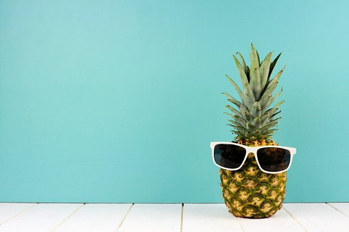 Hipster pineapple with sunglasses against turquoise 945897934