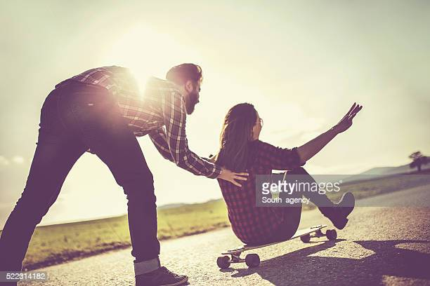 Hipster pushing girl on a longboard