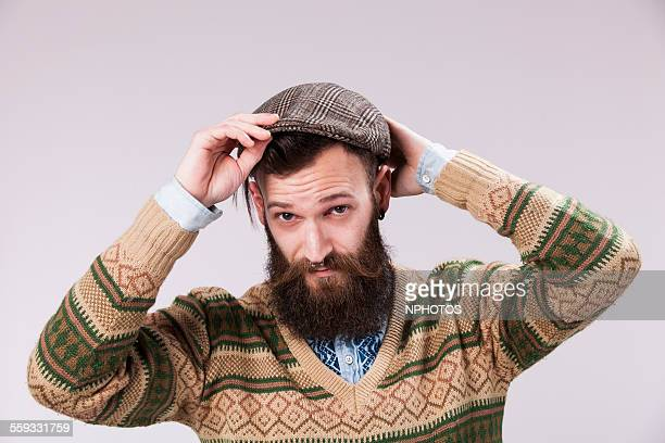 hipster puting his beret - flat cap stock pictures, royalty-free photos & images