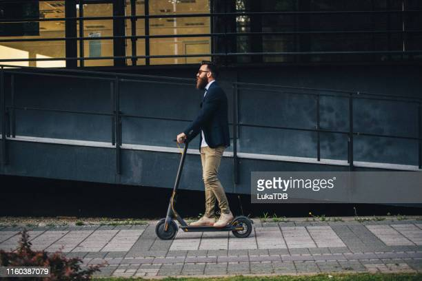 hipster riding a scooter in the city - mobility scooter stock photos and pictures
