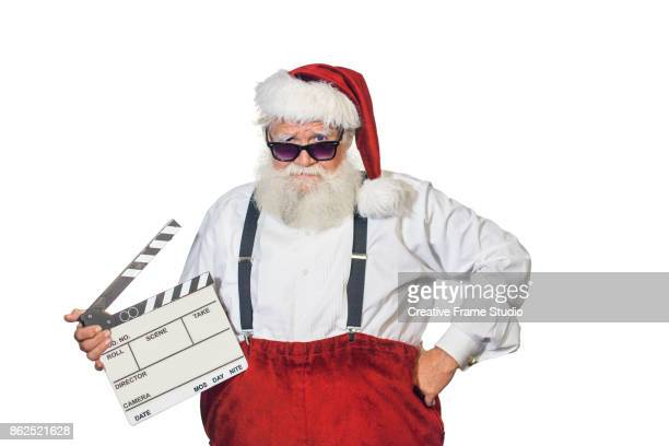Hipster Santa Claus holding a film clapperboard looking to camera above his sunglasses with a cool attitude wearing a white shirt with suspenders