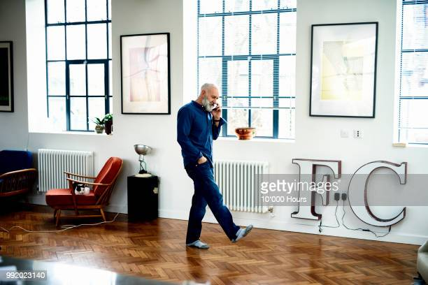 hipster senior man on cell phone in funky apartment - telefoon gebruiken stockfoto's en -beelden