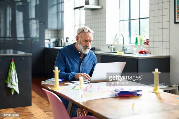 hipster senior man using laptop with map on table - solo un uomo anziano foto e immagini stock