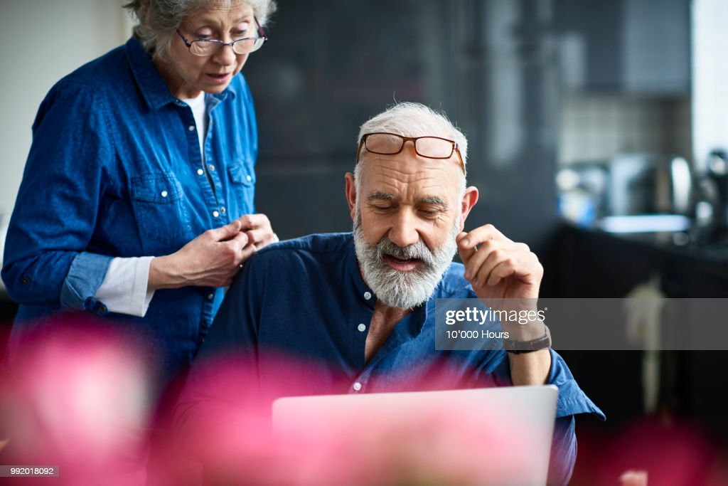 Hipster senior man with beard using laptop and woman watching : Stock-Foto