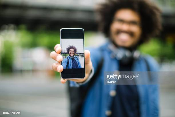 hipster showing his selfie - showing stock pictures, royalty-free photos & images