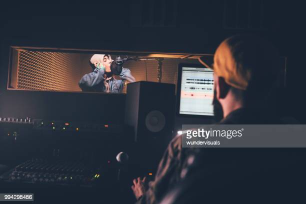 hipster singer and music producer recording music in professional studio - producer stock pictures, royalty-free photos & images