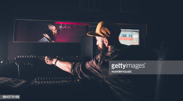hipster singer and music producer recording songs in music studio - sound recording equipment stock pictures, royalty-free photos & images