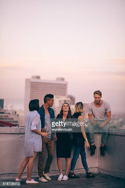 Hipster style friends celebrating a summer rooftop party