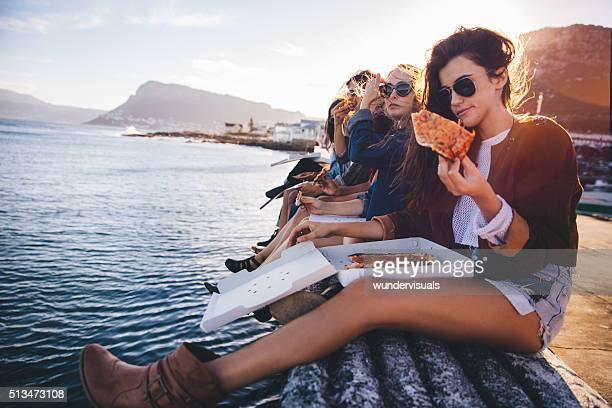 Hipster style teenager friends eating pizza on the dock