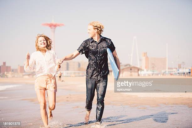 Hipster surfer couple running on the beach, Brooklyn New York