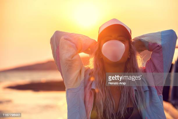 hipster teenage girl blowing pink bubble gum at sunset - bubble gum stock pictures, royalty-free photos & images