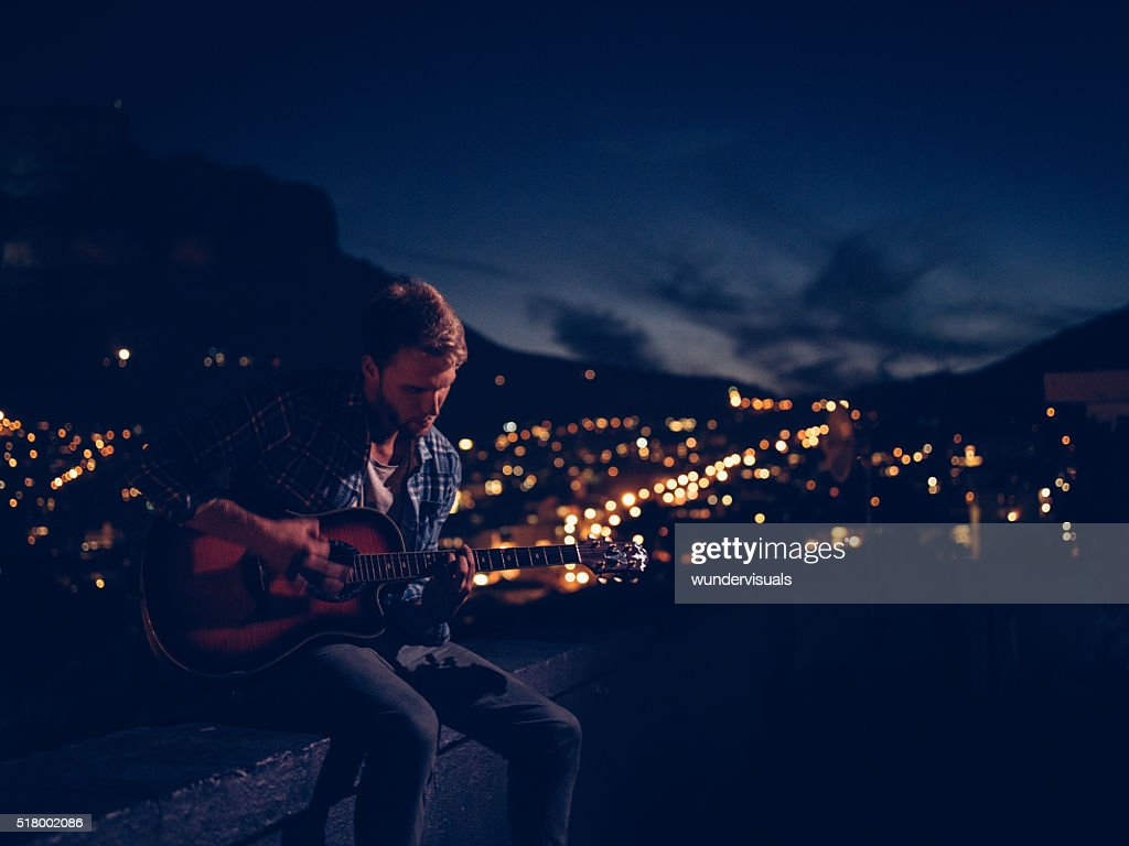 Hipster Teenager Boy Plays Guitar Sitting On Rooftop At Night Stock