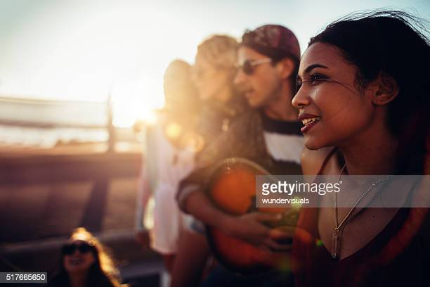 Hipster teenager friends relaxing at beach with a guitar