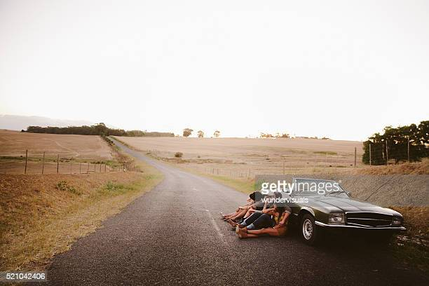 Hipster teenager friends relaxing near to a vintage convertible outside
