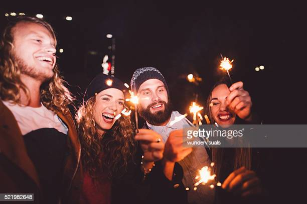 Hipster teenagers celebrating their friendship with sparklers at night